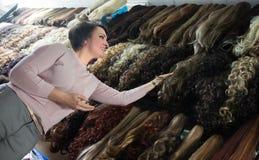 Vrouw het kopen bij de verschillende uitbreidingen van het kleurenhaar stock foto's