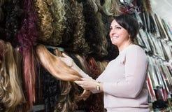 Vrouw het kopen bij de verschillende uitbreidingen van het kleurenhaar stock afbeelding