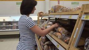 Vrouw het kopen brood in de supermarkt stock video