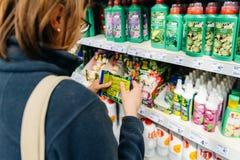 Vrouw het kopen installatiemeststof in DIY-opslag het tuinieren opslag Stock Afbeeldingen