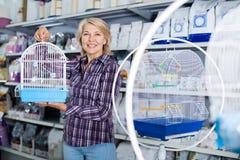 Vrouw het kopen kooi voor vogel in winkel stock fotografie