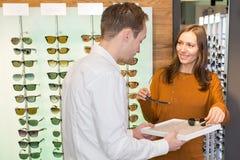 Vrouw het kopen zonnebril stock afbeelding