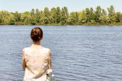 Vrouw het Letten op aan de Rivier stock fotografie