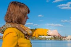 Vrouw het letten op horloge, portret op landschapsachtergrond royalty-vrije stock foto