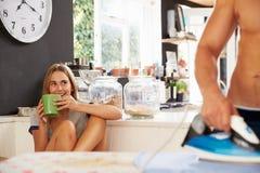 Vrouw het Letten op Man het Strijken Overhemd in Keuken stock foto