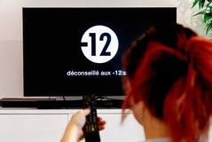 Vrouw het letten op televisie dat Frans ontkenningsbericht toont royalty-vrije stock foto's