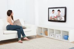 Vrouw het letten op televisie terwijl het zitten op bank Stock Foto