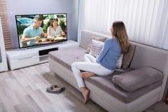 Vrouw het letten op televisie thuis stock foto
