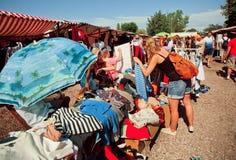 Vrouw het letten op tweede handoverhemden in een openluchtmarkt Stock Afbeelding