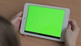 Vrouw het letten op video's op tablet, het groene scherm stock videobeelden