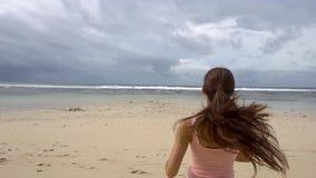 Vrouw het lopen aan zeewater en heft wapens op genietend van vrijheid op strand bij zonsopgang stock footage