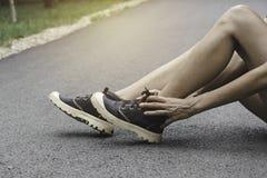 Vrouw het lopen op de weg krijgt ongeval op haar enkel het beeld voor gezondheidsconcept is stock afbeeldingen