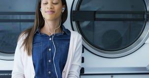 Vrouw het luisteren muziek op mobiele telefoon bij laundromat 4k stock footage