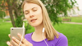 Vrouw het luisteren muziek op mobiele telefoon met oortelefoons in park Het gebruiken van haar smartphone, het dansen en het zing stock videobeelden