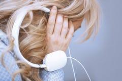 Vrouw het luisteren muziek via hoofdtelefoons Stock Foto's