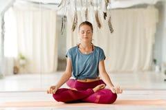 Vrouw het mediteren in lotusbloem stelt bij yogastudio royalty-vrije stock afbeelding