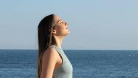 Vrouw het ontspannen ademhalings verse lucht op het strand stock videobeelden