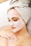 Vrouw het ontspannen in badkuip met gezichtsmasker Stock Foto's