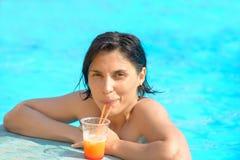 Vrouw het ontspannen bij de pool met kosmopolitische cocktail in de zomer stock afbeeldingen