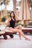 Vrouw het ontspannen in chaise zitkamer bij poolside op de zomerroeping bij toevlucht stock afbeelding