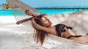 Vrouw het ontspannen in de hangmat op tropisch strand, de zomervaction Het vrije meisje koelen op exotisch eiland royalty-vrije stock fotografie