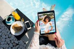 Vrouw het ontspannen door de pool en het lezen van emagazine op tablet bij ontbijt worden Alle inhoud omhoog gemaakt stock fotografie