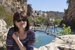 Vrouw het ontspannen door een meer met brug Stock Afbeelding