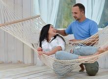 Vrouw het ontspannen in hangmat die en man status glimlachen royalty-vrije stock afbeelding