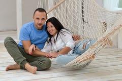 Vrouw het ontspannen in hangmat het glimlachen en man zitting stock foto