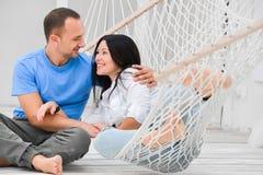 Vrouw het ontspannen in hangmat het glimlachen en man zitting Stock Afbeelding