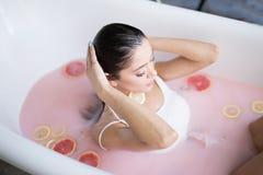 Vrouw het ontspannen in melkachtig bad in kuuroordtoevlucht Wellness en welzijnsconcept stock afbeeldingen