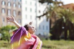 Vrouw het ontspannen met open wapens en gezicht aan zon Royalty-vrije Stock Afbeeldingen