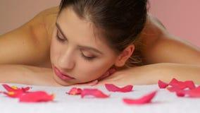 Vrouw het ontspannen na massage die op handdoeken met roze bloemblaadjes liggen stock videobeelden