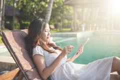 Vrouw het ontspannen naast de pool en het gebruiken van tablet Royalty-vrije Stock Foto