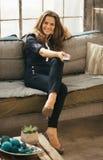 Vrouw het ontspannen op bank en het letten op TV in zolderflat Royalty-vrije Stock Foto
