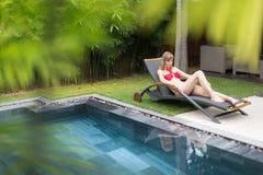 Vrouw het ontspannen op chaise-longue dichtbij pool Royalty-vrije Stock Afbeelding