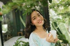 Vrouw het ontspannen op de kop van de balkonholding van koffie of thee stock afbeeldingen