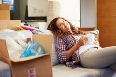 Vrouw het Ontspannen op het Nieuwe Huis van Sofa With Hot Drink In Royalty-vrije Stock Afbeelding