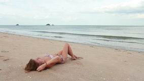 Vrouw het ontspannen op het strand dichtbij overzees stock videobeelden