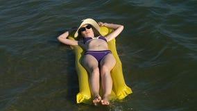 Vrouw het ontspannen op opblaasbare matras bij het strand stock videobeelden
