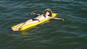 Vrouw het ontspannen op opblaasbare matras bij het strand stock video