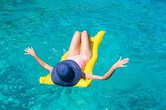 Vrouw het ontspannen op opblaasbare matras in duidelijke overzees Royalty-vrije Stock Foto's