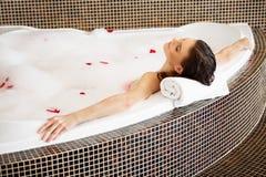 Vrouw het Ontspannen in Schuimbad met Rose Petals De voet van de vrouw in het water stock afbeeldingen