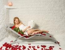 Vrouw het ontspannen in zoute ruimte met boek, rozen en bloemblaadjes Royalty-vrije Stock Afbeelding
