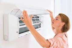 Vrouw het Openen Airconditioner Stock Foto's