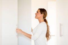 Vrouw het openen garderobe Stock Afbeelding