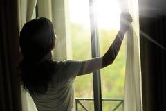 Vrouw het openen gordijnen in een slaapkamer Stock Fotografie