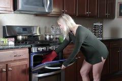 Vrouw het openen oven stock afbeelding
