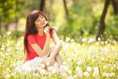 Vrouw in het park met paardebloemen Stock Afbeelding