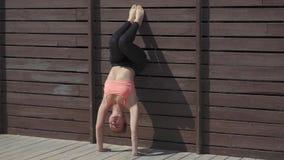 Vrouw het praktizeren de yogahandstand stelt op muur bij zonnige dag stock videobeelden